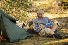 Senior man sitting outside a tent reading a book royalty free stock photography