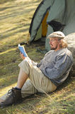 Senior man sitting outside a tent reading a book royalty free stock photo