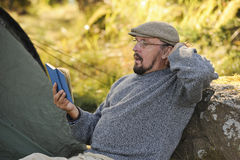 Senior man sitting outside a tent reading a book Royalty Free Stock Image