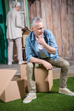 Senior man sitting on pile of cardboard boxes near new house Royalty Free Stock Photos