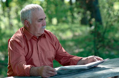Senior man sitting reading a newspaper Stock Images