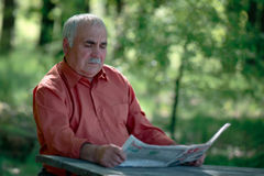 Senior man sitting reading a newspaper Stock Photography
