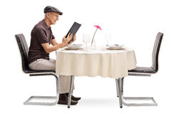 Senior man sitting at a restaurant table. And looking at the menu isolated on white background Royalty Free Stock Photo