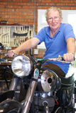 Senior Man Sitting On Restored Vintage Motorcycle Royalty Free Stock Photography