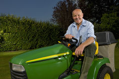Senior man sitting on riding lawn mower Royalty Free Stock Photo