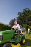 Senior man sitting on riding lawn mower Stock Photo