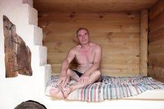 Senior man sitting on Russian stove Stock Image
