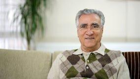 Senior man sitting on sofa Royalty Free Stock Photos