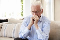 Senior Man Sitting On Sofa At Home Suffering From Depression stock photo