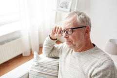 senior man sitting on sofa at home and thinking Stock Image