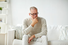 Senior man sitting on sofa at home and thinking Royalty Free Stock Image