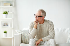 Senior man sitting on sofa at home and thinking Royalty Free Stock Photography