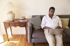 Senior Man Sitting On Sofa At Home Using Laptop Royalty Free Stock Images