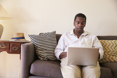 Senior Man Sitting On Sofa At Home Using Laptop Royalty Free Stock Images