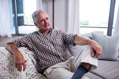 Senior man sitting on sofa in living room Royalty Free Stock Photography
