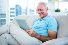 Senior man sitting on sofa while using digital tablet Royalty Free Stock Image