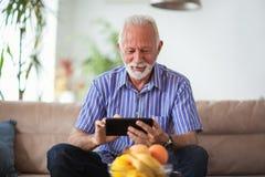 Senior man sitting on sofa and using digital tablet royalty free stock photography