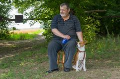 Man sitting on a stool next to his four-legged friend basenji dog in summer park Stock Photography