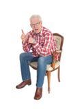 Senior man sitting surprised. Royalty Free Stock Photo