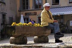 Senior man sitting in the swiss village Gruyeres, Switzerland. Royalty Free Stock Photos