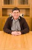 Senior man sitting at table with copyspace below Stock Image