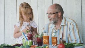 Grandfather with granddaughter tastes smoothies. Senior man sitting at the table with litle cute girl and tastes different smoothies, detox fresh vegetables stock footage