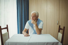 Senior man sitting at a table Stock Images