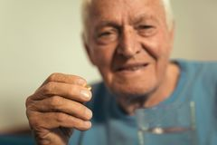Senior man sitting taking medication Royalty Free Stock Photography