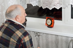 Senior man sitting waiting at night with a clock. Senior man sitting waiting in front of a window at night with a clock in front of him as he counts down the Royalty Free Stock Photography