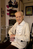 Senior Man Sitting in Wheel Chair in Care Facility. A senior man sitting in his room at a long term care facility surrounded by images and things special to him Stock Image