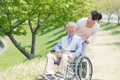 Senior man sitting on a wheelchair with caregiver Stock Images