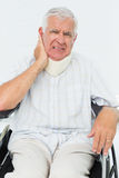 Senior man sitting in wheelchair with cervical collar. Portrait of a senior man sitting in wheelchair with cervical collar at the medical office stock photo