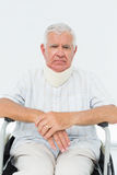 Senior man sitting in wheelchair with cervical collar. Portrait of a sad senior man sitting in wheelchair with cervical collar at the medical office royalty free stock image