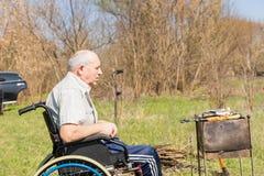 Senior Man Sitting on Wheelchair Grilling Outside Stock Photos