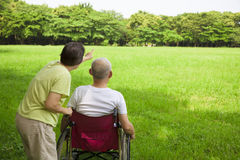 Senior man sitting on a wheelchair with his wife Stock Photos