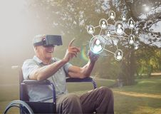 Senior man sitting on wheelchair using virtual reality headset and network connecting icons. Digital composition of senior man sitting on wheelchair using Stock Photos
