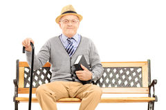 Senior man sitting on a wooden bench with book Stock Photography