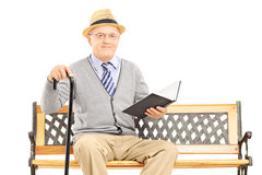 Senior man sitting on a wooden  bench and reading a book Stock Image
