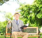 Senior man sitting on a wooden bench and reading a book, in a pa Stock Images