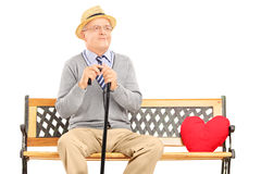 Senior man sitting on a wooden bench with red heart next to him Royalty Free Stock Photography