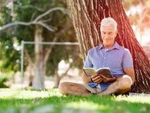 Senior man sittingin park while reading book Stock Photos