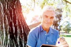 Senior man sittingin park while reading book Stock Images