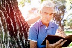 Senior man sittingin park while reading book Royalty Free Stock Photography