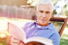 Senior man sittingin park while reading book Stock Image