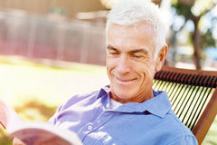 Senior man sittingin park while reading book Stock Photo