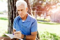 Senior man sittingin park while reading book Royalty Free Stock Image