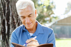 Senior man sittingin park while reading book Royalty Free Stock Photo