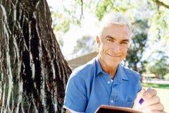 Senior man sittingin park while reading book Royalty Free Stock Images