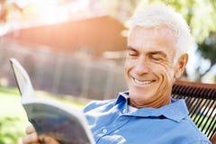 Senior man sittingin park while reading book Royalty Free Stock Photos