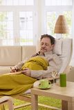 Senior man sleeping in armchair. Senior man lying in armchair, fell asleep while reading book Royalty Free Stock Photography